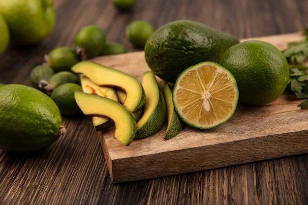 Vista superior de abacate em forma de pêra com fatias em uma placa de cozinha de madeira com limas feijoas isoladas em um fundo de madeira
