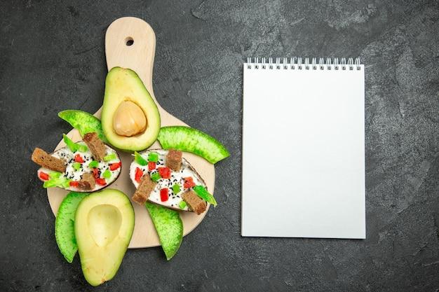 Vista superior de abacates cremosos com pão e pimenta e abacates frescos na superfície cinza