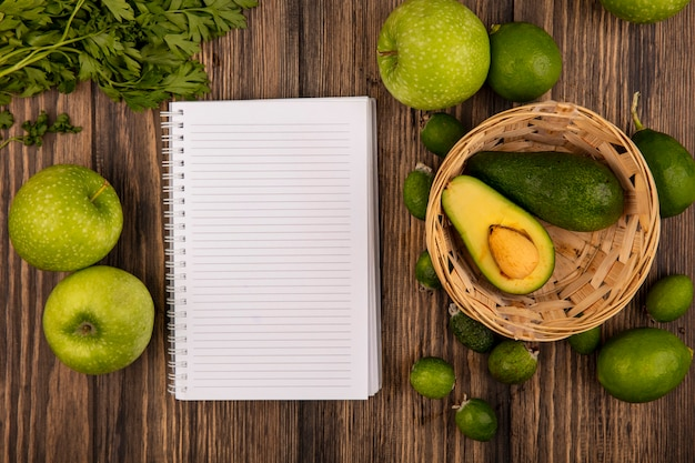 Vista superior de abacates frescos em um balde com maçãs verdes, limes, feijoas e salsa isoladas em um fundo de madeira com espaço de cópia