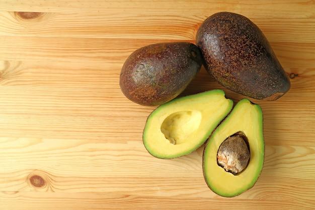 Vista superior de abacates maduros, frutas inteiras e corte ao meio isolado no fundo de madeira