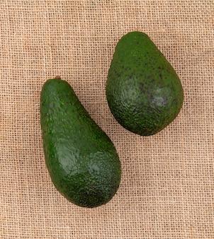 Vista superior de abacates saudáveis frescos verdes na superfície do pano de saco