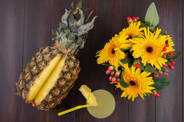 Vista superior de abacaxi e suco de abacaxi em vidro com tubo de beber e flores na superfície de madeira