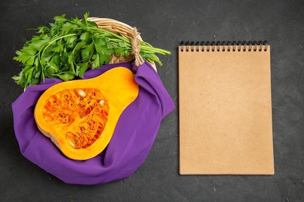 Vista superior de abóbora fresca com verduras dentro da cesta em fundo escuro