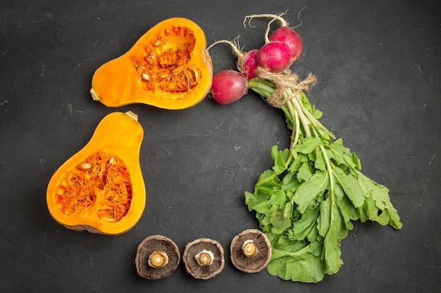 Vista superior de abóbora fresca com verduras e rabanete em comida de piso escuro