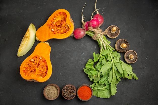 Vista superior de abóbora fresca com verduras e rabanete na mesa escura
