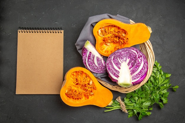 Vista superior de abóbora fresca com verduras e repolho roxo em fundo escuro