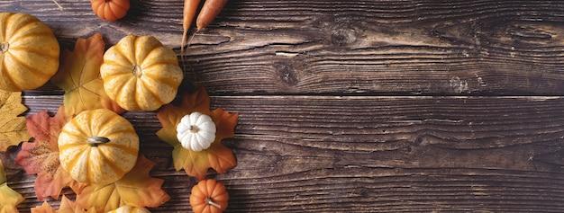 Vista superior de abóboras frescas e folhas de outono em uma superfície de madeira