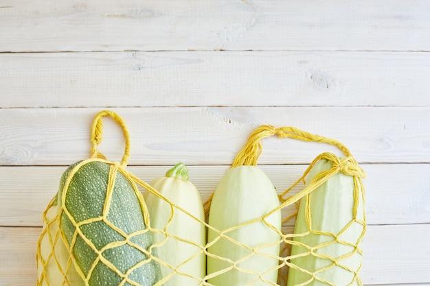 Vista superior de abobrinhas frescas em saco de linha sobre madeira