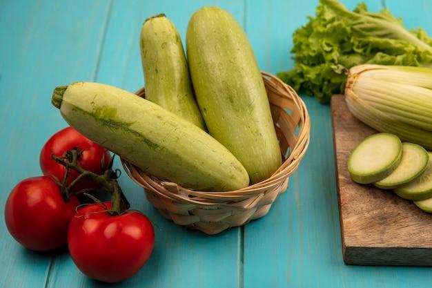Vista superior de abobrinhas frescas em um balde com alface aipo e abobrinhas picadas em uma placa de cozinha de madeira com tomates isolados em uma superfície de madeira azul
