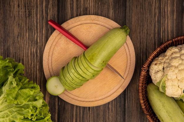 Vista superior de abobrinhas frescas picadas em uma placa de cozinha de madeira com uma faca com legumes, como abobrinhas e couve-flor em um balde em um fundo de madeira