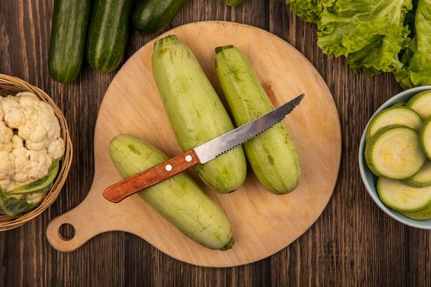 Vista superior de abobrinhas isoladas em uma placa de cozinha de madeira com faca com couve-flor em um balde com pepinos e alface isoladas em uma superfície de madeira