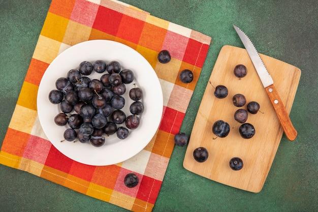 Vista superior de abrunhas roxas escuras em um prato branco em uma toalha de mesa xadrez com abrunhas isoladas em uma placa de cozinha de madeira com uma faca em um fundo verde