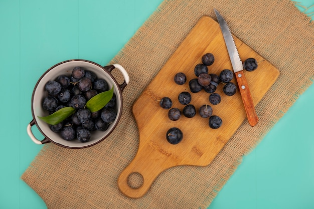 Vista superior de abrunhas roxas escuras em uma placa de cozinha de madeira com uma faca em um pano de saco sobre um fundo azul