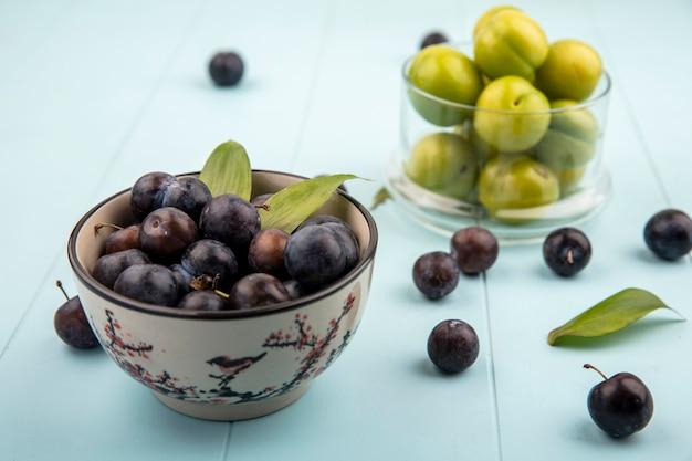 Vista superior de abrunhos azedos roxos escuros em uma tigela com ameixas de cereja verdes frescas em uma jarra de vidro sobre um fundo azul