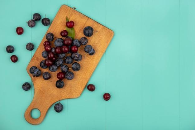 Vista superior de abrunhos roxos escuros com cerejas em uma placa de cozinha de madeira em um fundo azul com espaço de cópia