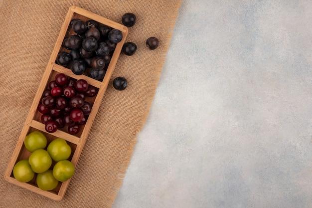 Vista superior de abrunhos roxos escuros com cerejas vermelhas e ameixas verdes em uma bandeja de madeira com pedaços em um pano de saco em um fundo branco com espaço de cópia