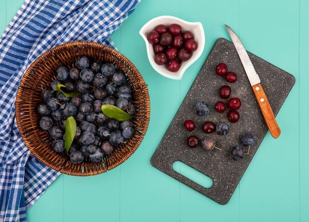 Vista superior de abrunhos roxos escuros em um balde com deliciosas cerejas vermelhas em uma tigela branca com abrunhos e cerejas em uma tábua de cozinha com faca em um fundo azul