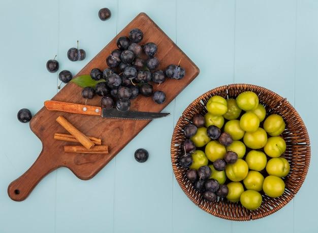 Vista superior de abrunhos roxos escuros em uma placa de cozinha de madeira com uma faca com paus de canela e ameixas de cereja verdes em um balde sobre um fundo azul