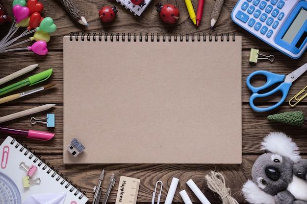 Vista superior de acessórios de capa e papelaria caderno em branco sobre fundo de madeira
