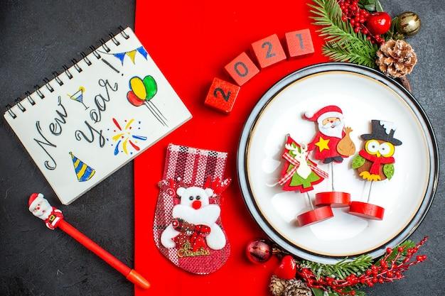 Vista superior de acessórios de decoração de prato de jantar ramos de abeto e números meia de natal em um guardanapo vermelho ao lado de um caderno com desenhos de ano novo em uma mesa preta