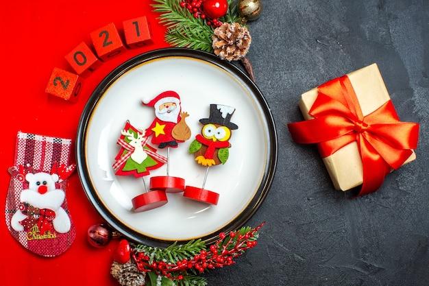 Vista superior de acessórios de decoração de prato de jantar ramos de abeto e números meia de natal em um guardanapo vermelho ao lado do presente em uma mesa preta