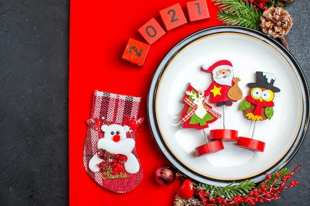 Vista superior de acessórios de decoração de prato de jantar ramos de abeto e números meia de natal em um guardanapo vermelho sobre uma mesa preta