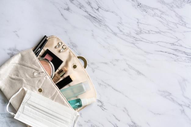 Vista superior de acessórios de mulher, desinfetante, spray de álcool e máscara protetora na bolsa, conceito de beleza. deve ter item no conceito 2020. copie o espaço, configuração plana