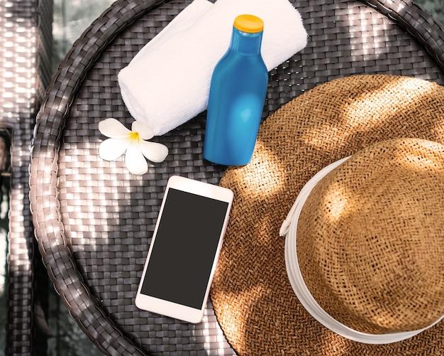 Vista superior de acessórios de praia. protetor solar, chapéu de palha, toalha e smartphone na mesa ao lado da piscina