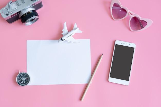 Vista superior de acessórios de viagem e papel na tabela de cores rosa, conceito de viagens. configuração plana, cópia espaço