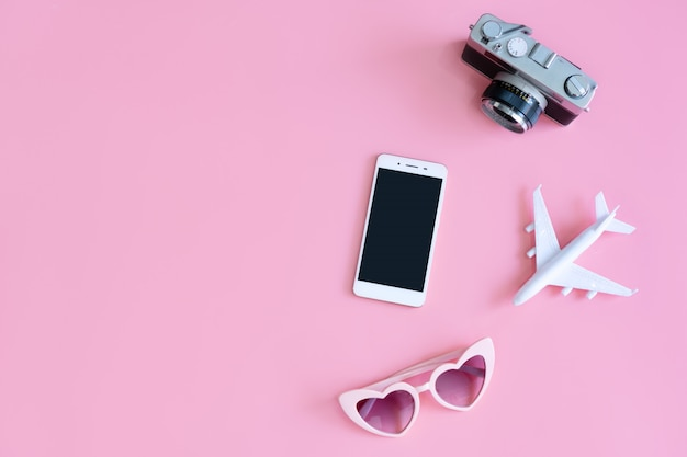Vista superior de acessórios de viagem em fundo de cor-de-rosa, conceito de viagens. configuração plana, cópia espaço