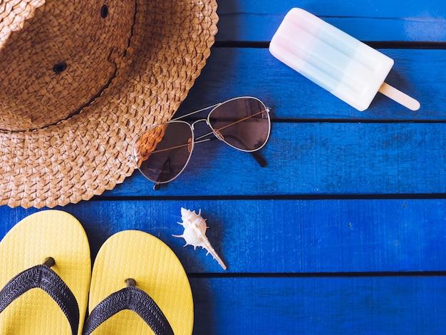 Vista superior de acessórios do verão no assoalho de madeira azul.