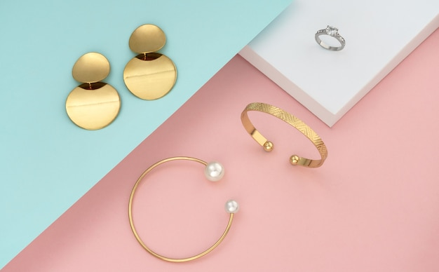 Vista superior de acessórios femininos dourados em papel de cores pastel