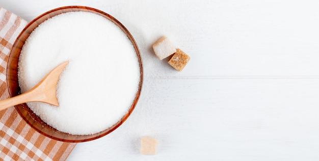 Vista superior de açúcar branco em uma tigela de madeira com uma colher e cubos de açúcar em fundo branco, com espaço de cópia