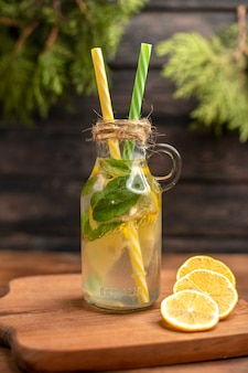 Vista superior de água desintoxicante fresca em um copo servido com tubos e limas de limão em uma tábua de madeira