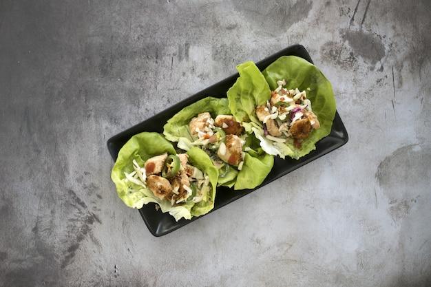Vista superior de alface embrulhada com vegetais e carne em uma placa preta na mesa
