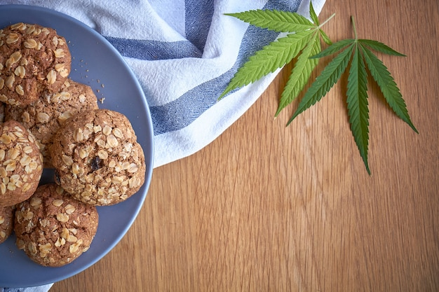 Vista superior de algumas cookies de potenciômetro da farinha de aveia em uma placa cinzenta em uma toalha listrada em uma superfície de madeira clara.