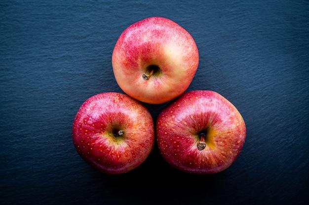 Vista superior de algumas maçãs vermelhas frescas em um fundo escuro. conceito de comida saudável e natural.