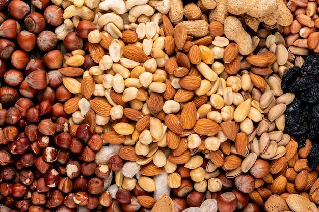 Vista superior de algumas nozes sortidas e frutas secas com nozes, pistache, amêndoa, amendoim, caju, pinhões.