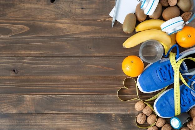 Vista superior de alguns alimentos naturais, tênis e fita métrica em um fundo de mesa de madeira escura. conceito de saúde, alimentação e esporte.
