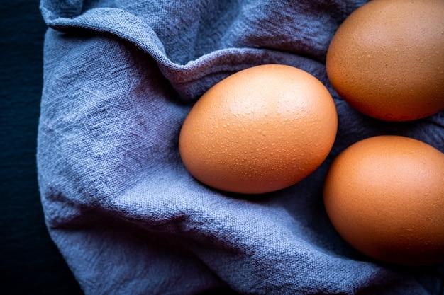 Vista superior de alguns ovos frescos em um fundo escuro conceito de comida saudável e natural.