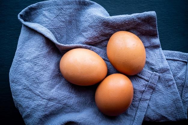 Vista superior de alguns ovos frescos no escuro. conceito de comida saudável e natural.