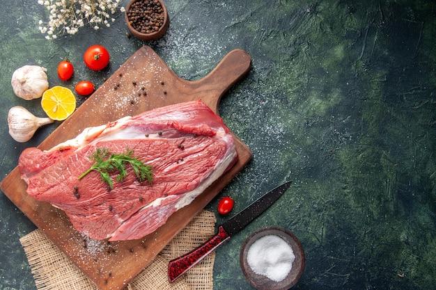 Vista superior de alhos frescos de carne vermelha crua na tábua de madeira, limão na faca de flor toalha de cor nude no lado direito em fundo de cor mista