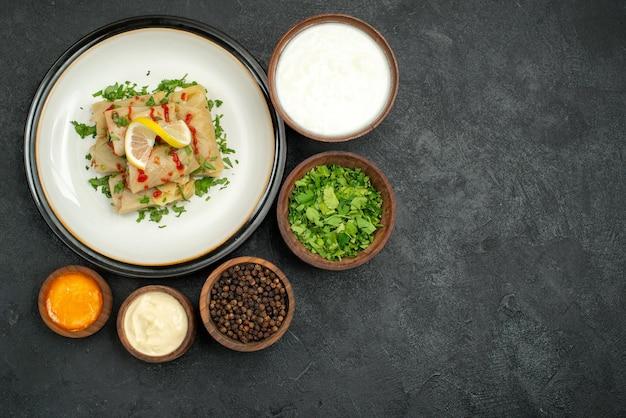 Vista superior de alimentos à distância em tigelas de mesa de ervas de creme de leite, pimenta preta e molho amarelo e repolho recheado com ervas de limão e molho na chapa branca na mesa preta