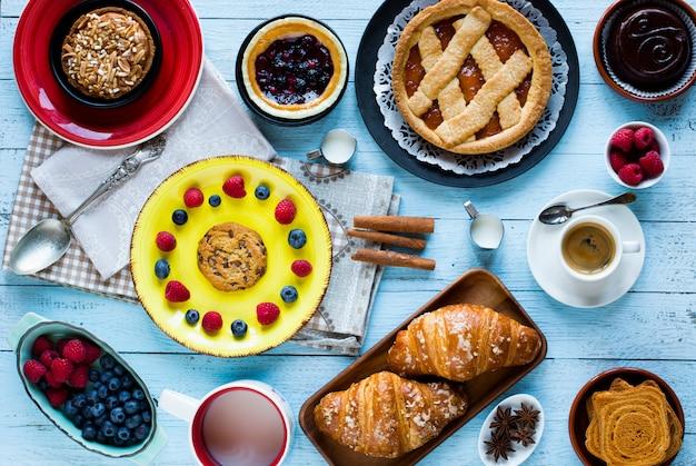Vista superior de alimentos doces clássicos de um café da manhã completo de madeira da tabela.