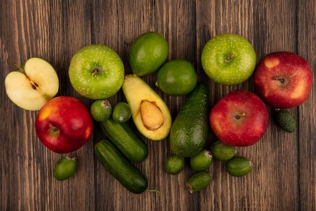 Vista superior de alimentos frescos, como maçãs verdes e vermelhas feijoas abacates pepinos isolados em uma superfície de madeira