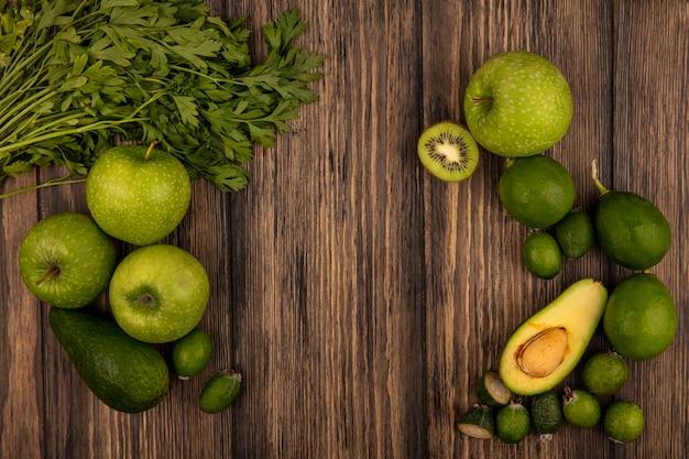 Vista superior de alimentos frescos, como maçãs verdes, limas, feijoas, abacates e salsa, isolada em uma parede de madeira com espaço de cópia