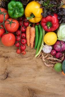 Vista superior de alimentos orgânicos na placa de madeira, composição com legumes orgânicos crus variados