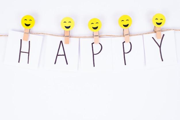 Vista superior de alto ângulo de um smiley alegre alegre pendurado em um cordão com a descrição feliz parede branca isolada