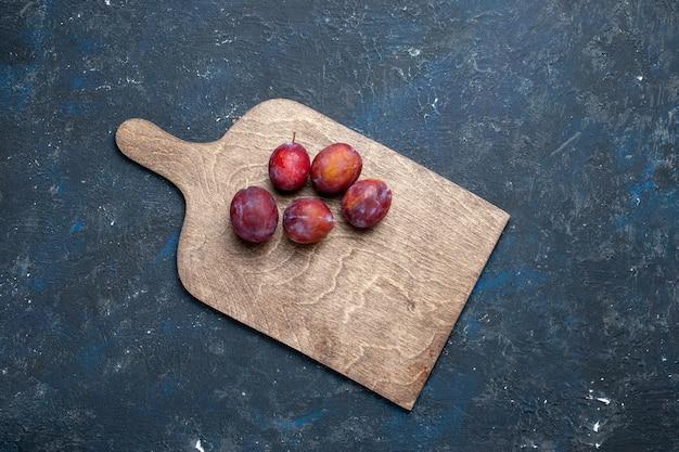 Vista superior de ameixas azedas frescas inteiras maduras e suculentas em frutas vermelhas escuras