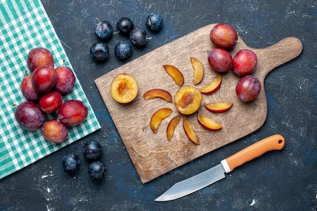 Vista superior de ameixas frescas inteiras maduras e suculentas cortadas em frutas cinza-escuras, vitaminas frescas de verão